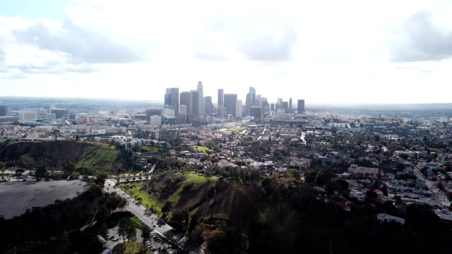 4k drone video of the downtown los angeles skyline and its surrounding houses and buildings - los angeles county stock videos & royalty-free footage