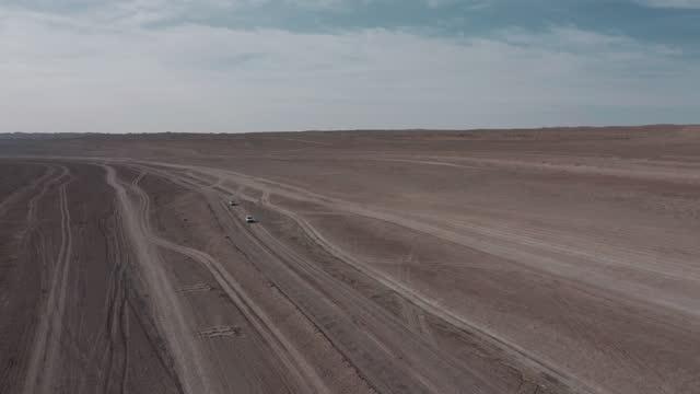 drone video of two cars driving in the desert land - china east asia bildbanksvideor och videomaterial från bakom kulisserna