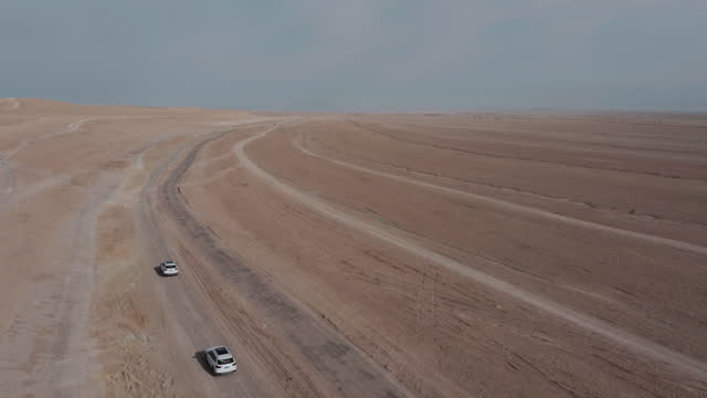drone video of two cars driving in the desert land - china east asia stock videos & royalty-free footage