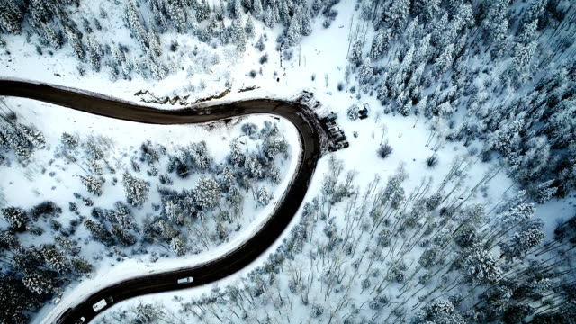 drone view above snow covered forest and curved highway winding through the mountains - santa fe new mexico stock videos & royalty-free footage