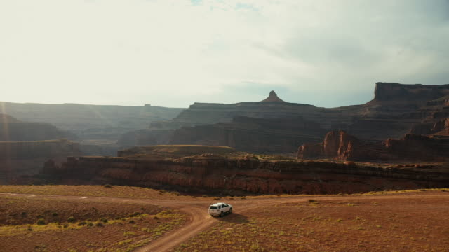 vídeos de stock, filmes e b-roll de opinião do zangão: carro na fuga canyonlands de shafer - pedra rocha