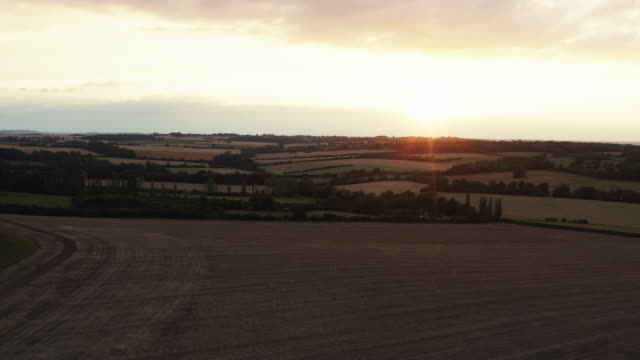 drone view clip across uk rural scene at sunset - meadow stock videos & royalty-free footage