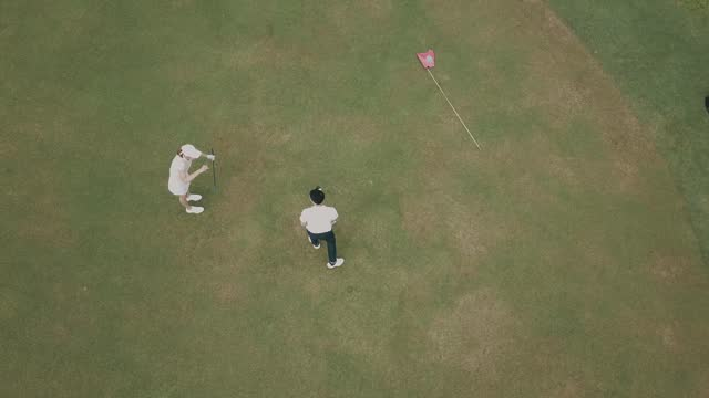 drone view directly above asian chinese male golfer line up golf ball near golf hole on the golf course with his companion - putting stock videos & royalty-free footage