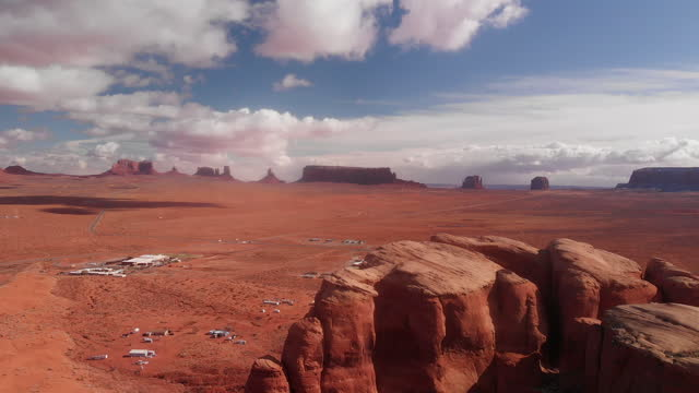 vídeos de stock e filmes b-roll de a drone view from teardrop arch looking over the amazing rock formations, the iconic monuments of monument valley and other spectacular rock formations - arco natural