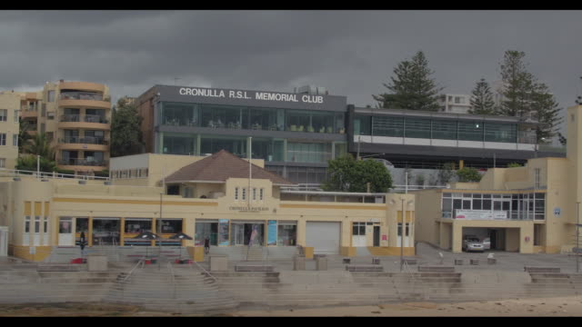 vídeos de stock e filmes b-roll de drone - view from the beach towards and across cronulla pavilion, surf life saving club and cronulla r.s.l memorial club, with dark clouds in... - maça