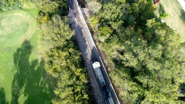 drone view looking down above railroad tracks and train crossing town lake bridge in austin , texas - cargo train stock videos & royalty-free footage