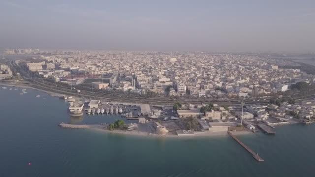 drone view moving towards muharraq showing a marina and the main road that rings the island. - ペルシャ湾点の映像素材/bロール