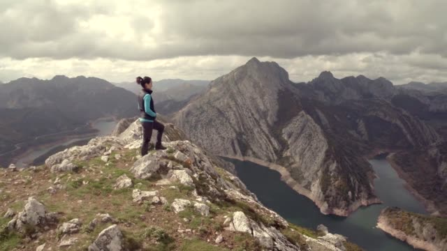drone view of a girl on the top of a mountain - wandern stock-videos und b-roll-filmmaterial