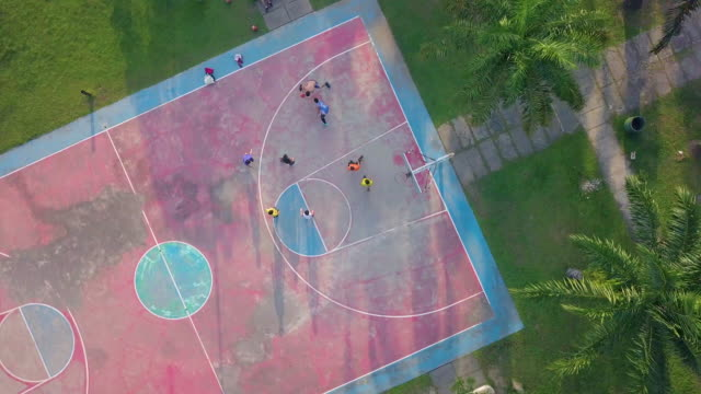 vídeos de stock, filmes e b-roll de drone view of a group of people playing basketball in basketball court - court