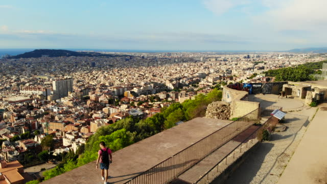 stockvideo's en b-roll-footage met drone view of a guy in the military bunkers viewpoint over barcelona city during sunrise. - draaien lichaamsbeweging