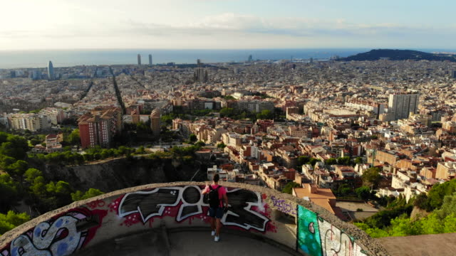 vídeos de stock e filmes b-roll de drone view of a guy in the military bunkers viewpoint over barcelona city during sunrise. - barcelona espanha