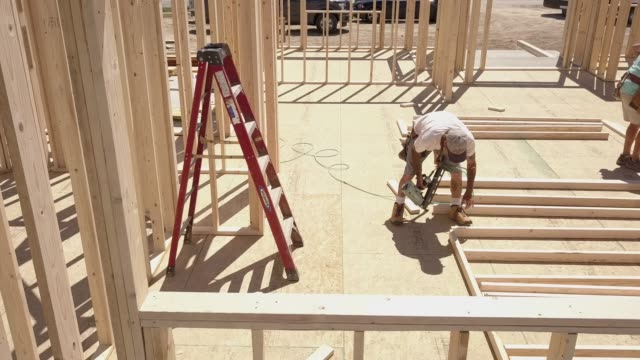 vídeos de stock e filmes b-roll de drone view of a home being framed by carpenters - moldura de quadro