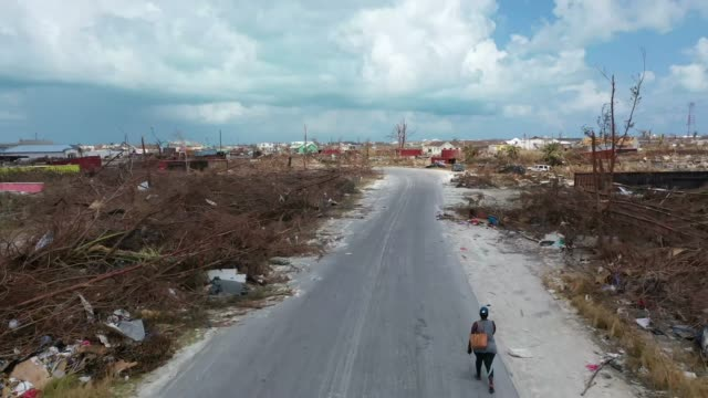 stockvideo's en b-roll-footage met drone view of a resident of marsh harbour walks on an empty road, at marsh harbour, bahamas, on september 11, 2019. hurricane dorian made landfall on... - bahama's
