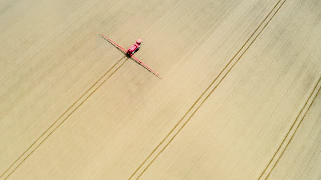drone view of a tractor spraying in a newly sown field - soil stock videos & royalty-free footage