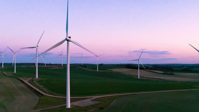 drone view of a wind farm at dusk - purple stock videos & royalty-free footage