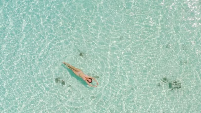 drone view of a woman floating and swimming on ocean - transparent stock videos & royalty-free footage
