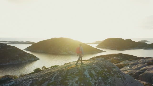 drone view of a woman outdoor adventures: hiking in norway, on the mountain by a fjord - hiking stock videos & royalty-free footage