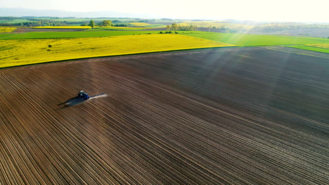 AGRICULTURE. Drone view of Agricultural tractor spraying field.