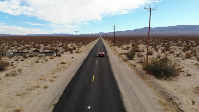 vidéos et rushes de drone view of american car driving in a straight road at the california desert. - route 66