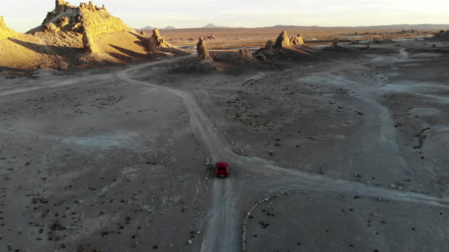 vidéos et rushes de drone view of american car driving through the rock formations in the california desert. - route 66