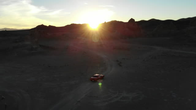 drone view of american car driving through the rock formations in the california desert. - sportwagen stock-videos und b-roll-filmmaterial