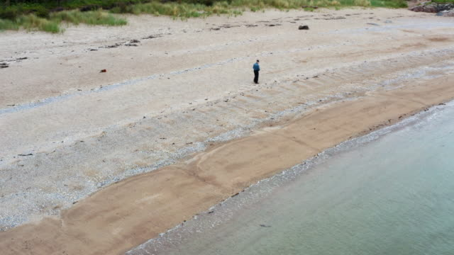 drone view of an active senior man walking along a scottish beach on a summer day - johnfscott stock videos & royalty-free footage