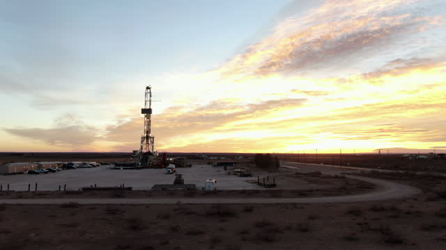 drone view of an oil or gas drill fracking rig pad with beautiful cloud filled sky at sunset - montana western usa stock videos & royalty-free footage
