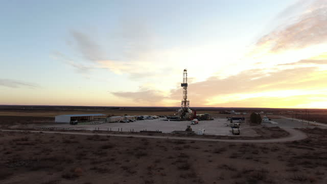 drone view of an oil or gas drill fracking rig pad with beautiful cloud filled sky at sunrise - montana western usa stock videos & royalty-free footage