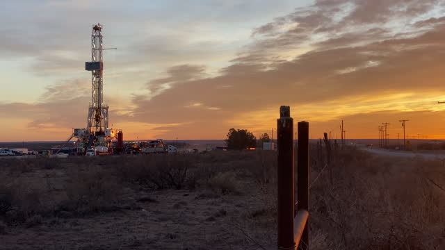 drone view of an oil or gas drill fracking rig pad with beautiful cloud filled sky - montana western usa stock videos & royalty-free footage