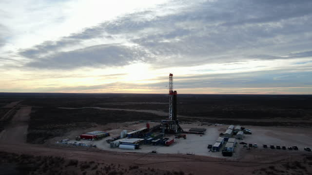drone view of an oil or gas drill fracking rig pad with beautiful cloud filled sky at dusk - montana western usa stock videos & royalty-free footage