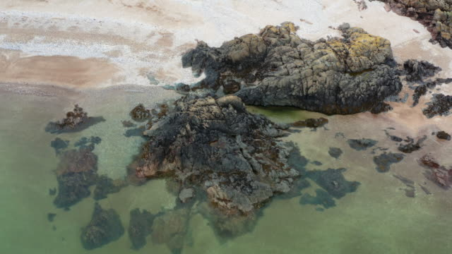 drone view of an outcrop of rocks on a scottish beach on a summer day - johnfscott stock videos & royalty-free footage
