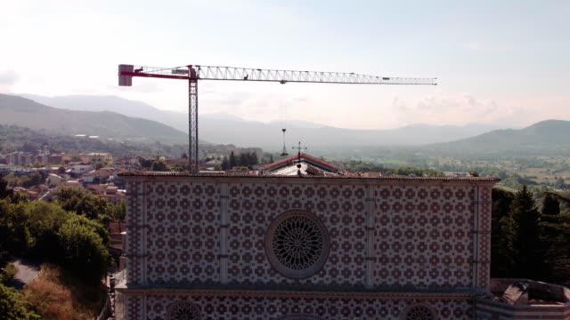 vídeos de stock e filmes b-roll de a drone view of basilica of men at work in santa maria di collemaggio in l'aquila on june 8 2017 the church was damaged in the last 2009 earthquake... - estilo do século 16