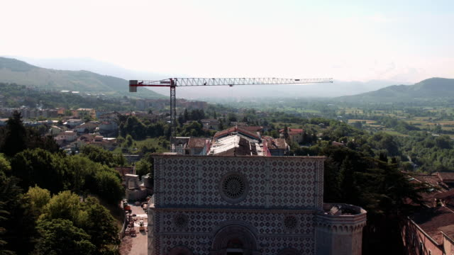 drone view of basilica of men at work in santa maria di collemaggio in l'aquila, on june 8, 2017. the church was damaged in the last 2009 earthquake... - stilrichtung des 16. jahrhunderts stock-videos und b-roll-filmmaterial