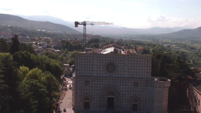 stockvideo's en b-roll-footage met a drone view of basilica of men at work in santa maria di collemaggio in l'aquila on june 8 2017 the church was damaged in the last 2009 earthquake... - 16e eeuwse stijl