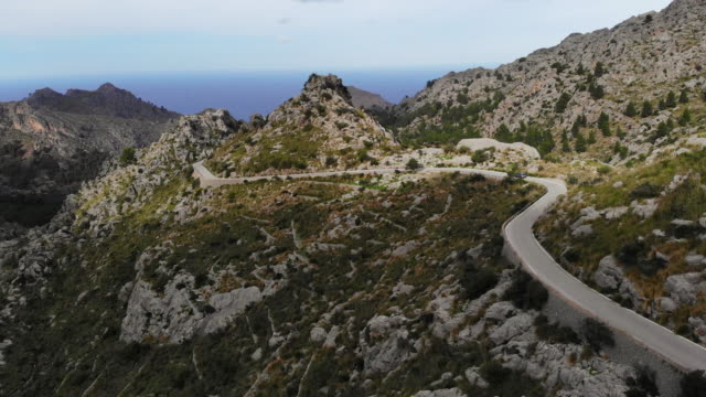 drone view of car driving stunning mountain road between the rocky terrain in the mountains of mallorca island. - mountain road stock videos & royalty-free footage