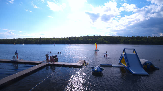 drone view of children at summer camp on a lake participating in a variety of water activities - swimwear stock videos & royalty-free footage