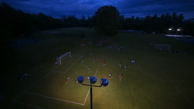 drone view of children playing a game of flag football in the evening - game night leisure activity stock videos & royalty-free footage