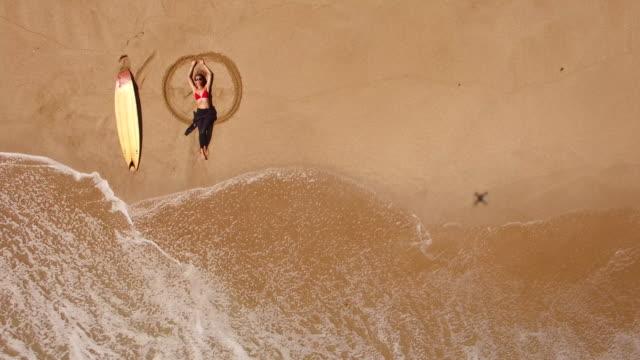 4K Drohne Blick auf Küste Surfer Frau am Strand liegen