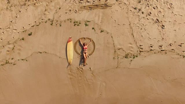 4k drönarvy av kustlinjen surfer kvinna på stranden - ängel bildbanksvideor och videomaterial från bakom kulisserna