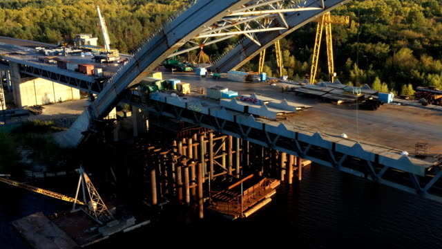 drone view of construction of podilsko-voskresenskyi bridge across dnieper river in kiev - キエフ市点の映像素材/bロール