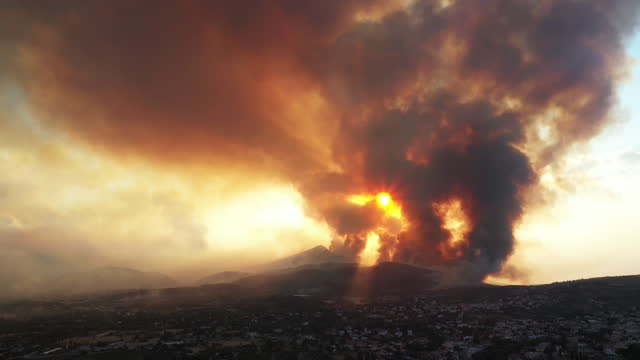 vídeos de stock, filmes e b-roll de drone view of dense smoke rising over the town of kapandriti as the wildfire continues to burn on mount parnitha about 35km north from athens, greece... - grécia