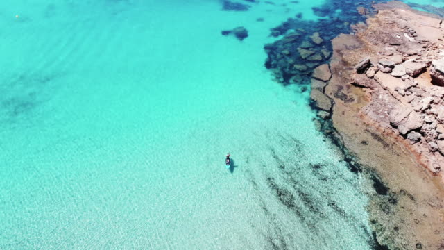 drone view of guy doing paddle surf in the crystal water of the formentera island with stunning landscape in spain. haciendo paddle surf ha vista de drone en la playa de formentera con vistas increibles. - seascape stock videos & royalty-free footage