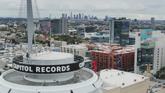 drone view of hollywood passing capitol records building with downtown la skyline - tower stock videos & royalty-free footage