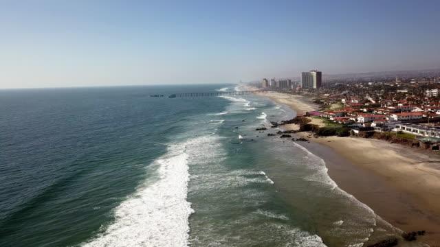 a drone view of playas de rosarito, mexico's rocky coastline with the waves crashing violently - baja california norte stock videos & royalty-free footage