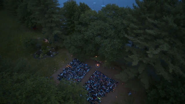 drone view of seated children at a busy summer camp at dusk - camping stock videos & royalty-free footage