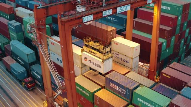 drohnenansicht von schiffscontainern in einem stark befahrenen hafen - box container stock-videos und b-roll-filmmaterial
