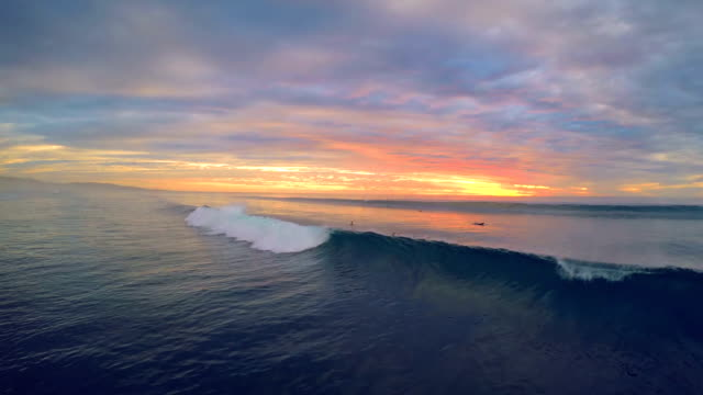 Drone view of surfing duck diving wave during sunset