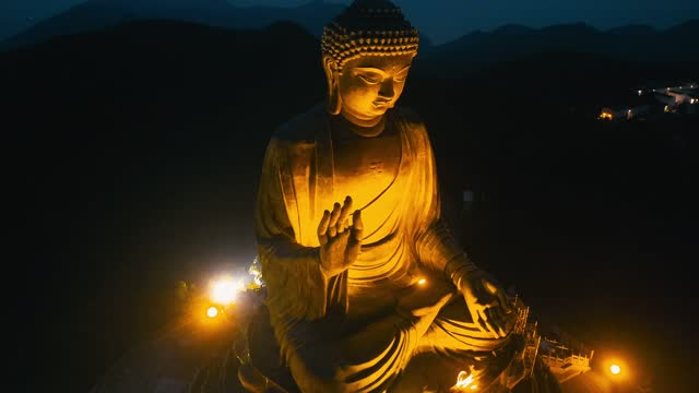 drone view of the big buddha is lit in the evening - buddha stock videos & royalty-free footage