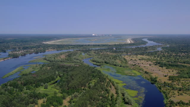 stockvideo's en b-roll-footage met drone view of the chernobyl's disaster area and the chernobyl nuclear power site from the bridge over pripyat, in pripyat, on june 17, 2019. the... - kernramp van tsjernobyl