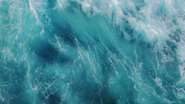 vídeos de stock e filmes b-roll de drone view of the ocean waves splashing - azul turquesa